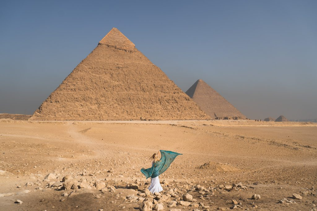 a girl twirls with a blue scarf in front of the pyramids during her trip to egypt