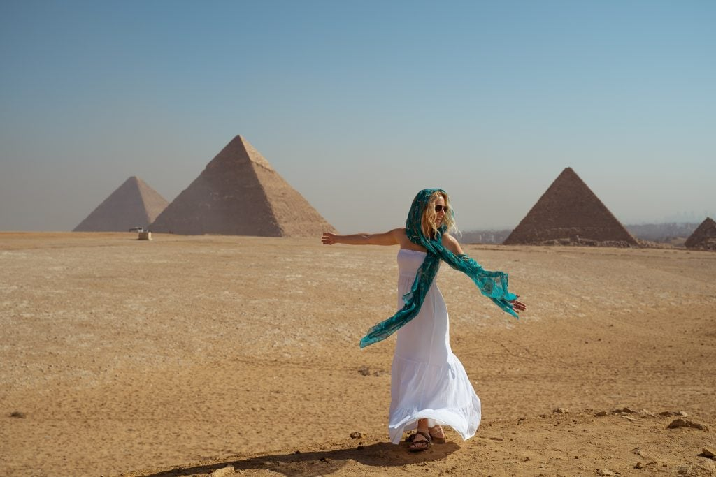 a girl in a white dress and blue head scarf spins in front of three pyramids during her trip to egypt