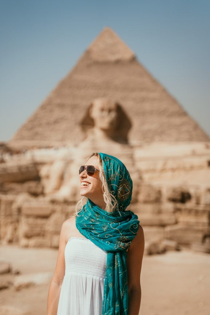 a girl in a white dress and blue headscarf smiles in front of the great sphinx of giza, with the third pyramid in the distance, during her trip to egypt