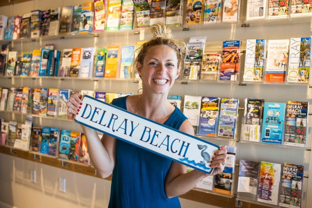 girl holds a delray beach sign