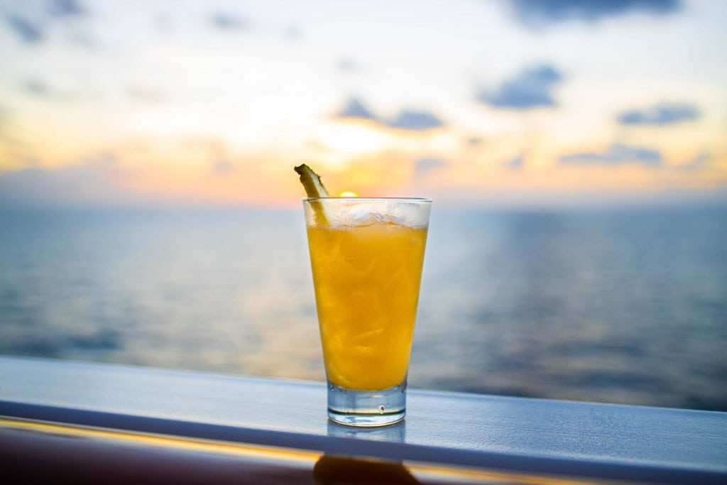a yellow cocktail overlooks the sunset on the norwegian encore