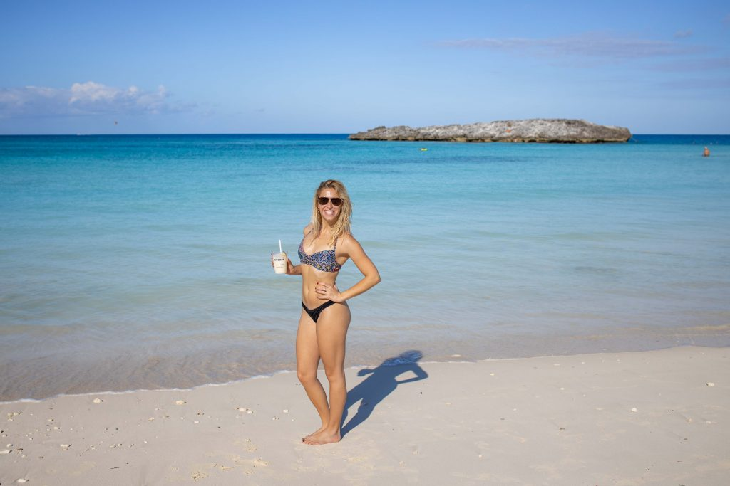a girl stands on the white-sand beaches of great stirrup cay in the bahamas