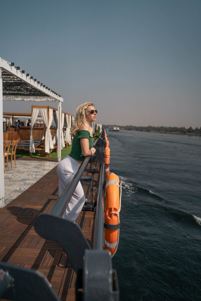 a girl looks out from the deck of a ship on her luxury nile cruise