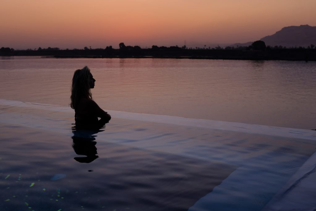 a girl stands by the edge of an infinity pool overlooking the nile at sunset