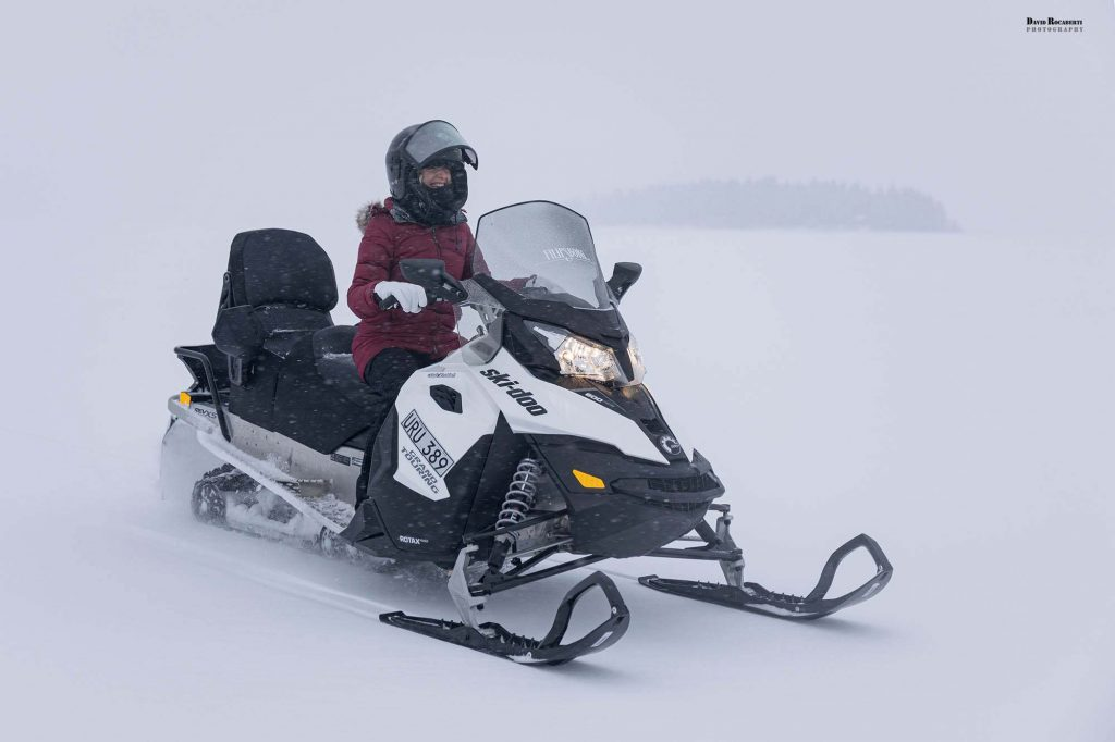 girl snowmobiles through the snow