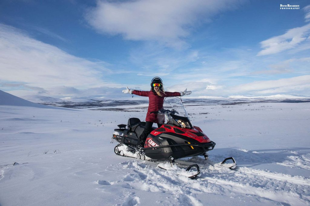 girl snowmobiles in lapland sweden
