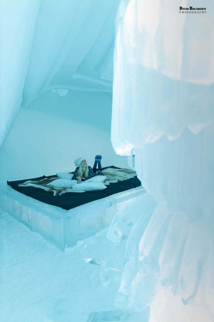 girl sleeps on a bed of ice at the icehotel in sweden