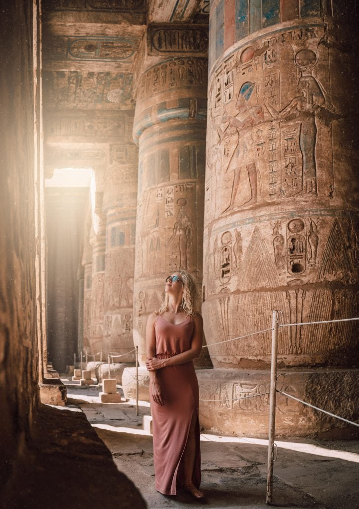 a girl wanders the halls of medinet habu temple in luxor egypt