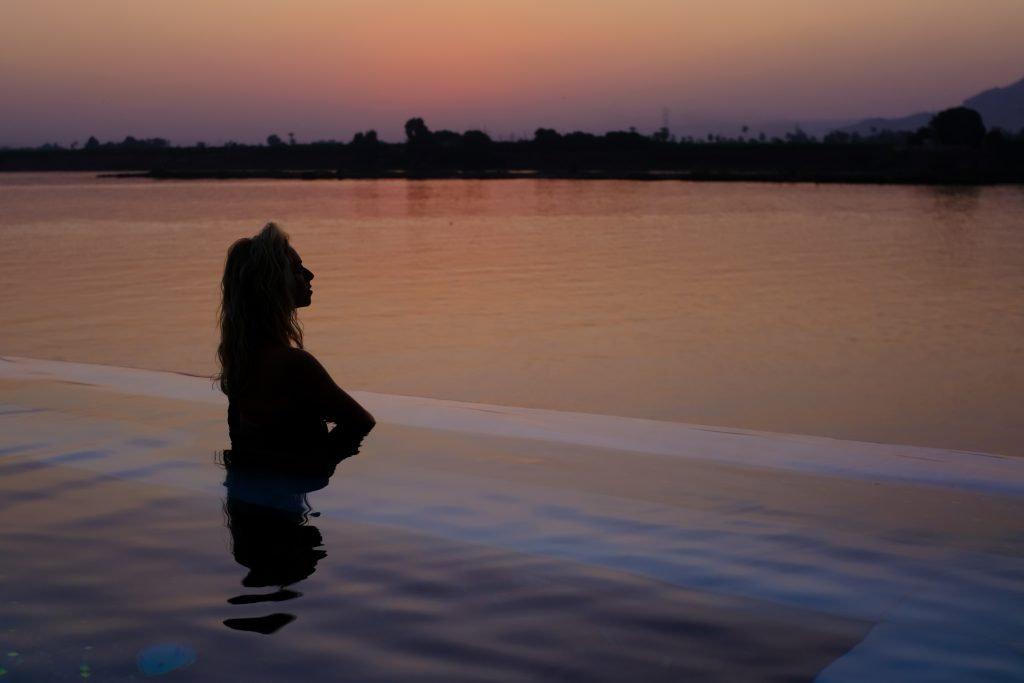 a girl sits at the edge of an infinity pool overlooking the nile at sunset