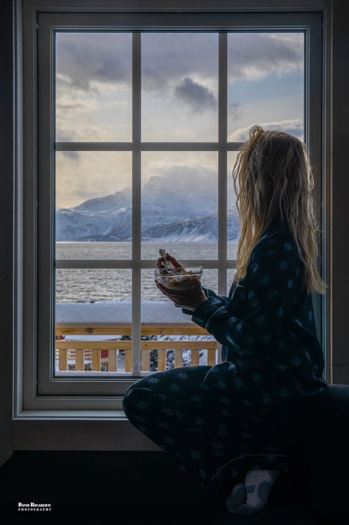 a girl looks out a window while eating breakfast, quarantined in norway during the coronavirus pandemic