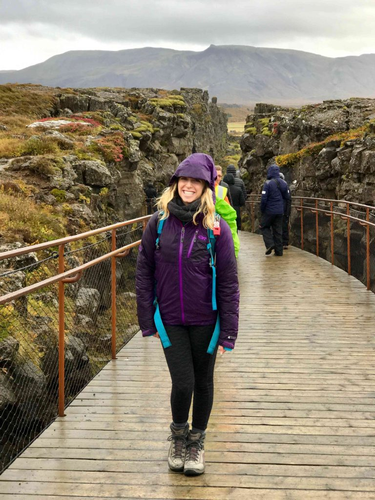 a girl stands between north america and europe at thingvellir national park
