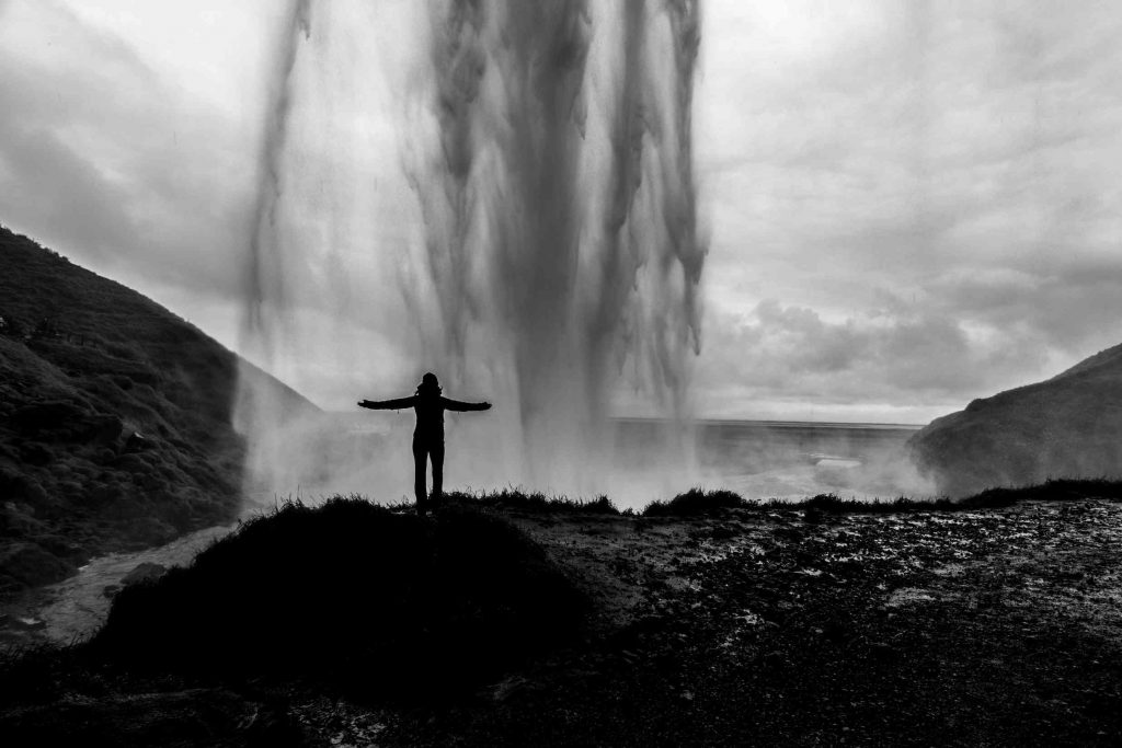 a girl stands behind a waterfall on her iceland holidays