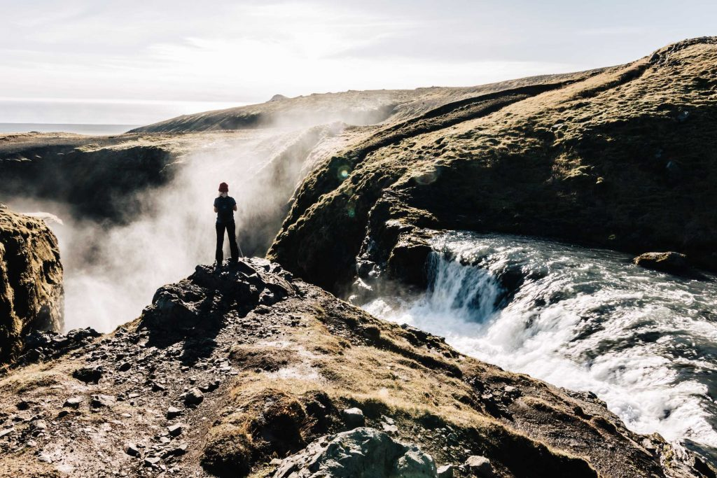 a girl stands atop skogafoss waterfall on her iceland holidays