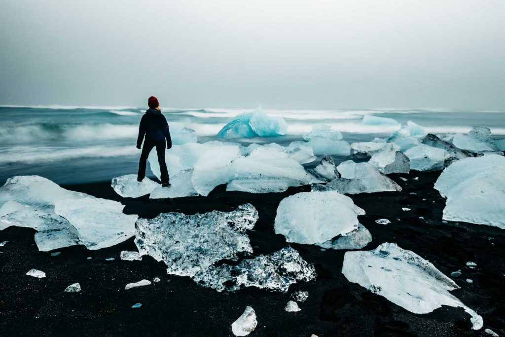 girl stands on ice on a beach in iceland - iceland holidays