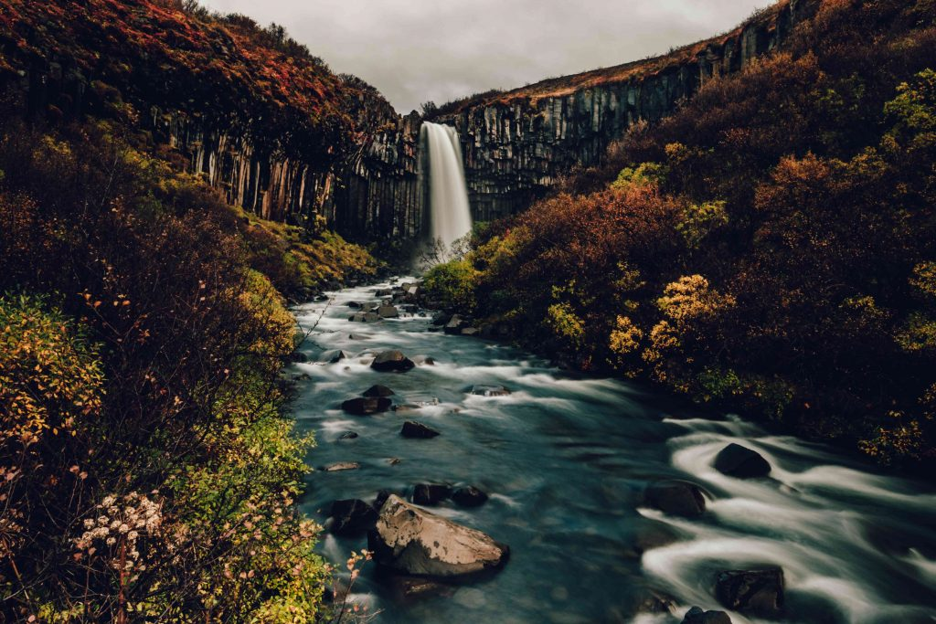 a waterfall in iceland surrounded by basalt columns