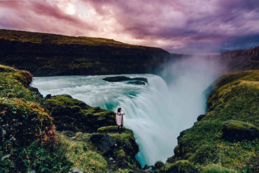 a girl stands overlooking gulfoss at sunset, a must when planning your iceland holidays