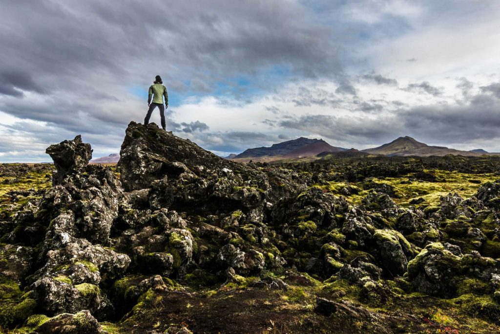 a man stands on a rock in a volcanic field during his iceland holidays