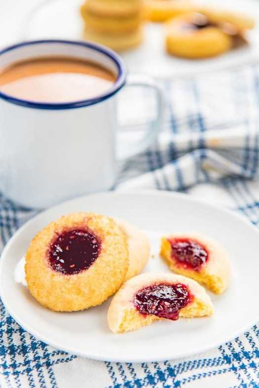 Three thumbprint cookies on a small white plate, with a mug of coffee in the background. The thumbprint cookie in the foreground broken in half.