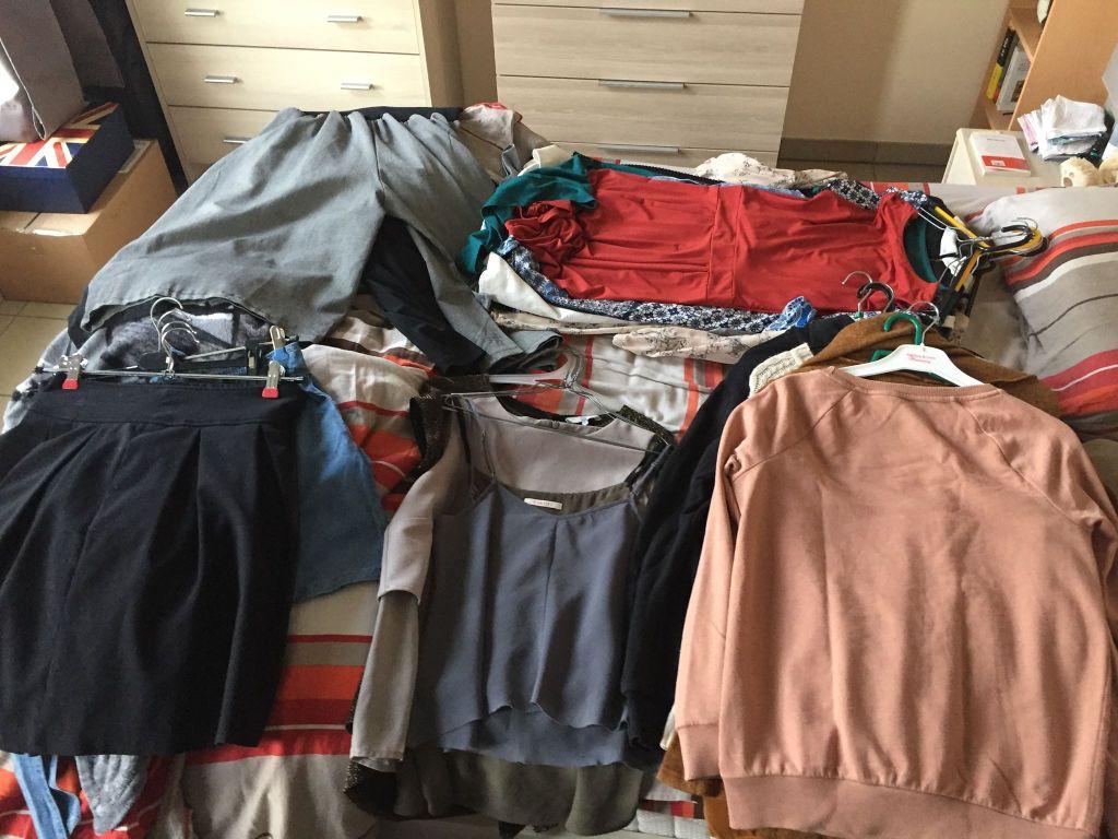 Vêtements assemblés en tas pour faire le tri avant de composer sa garde-robe capsule