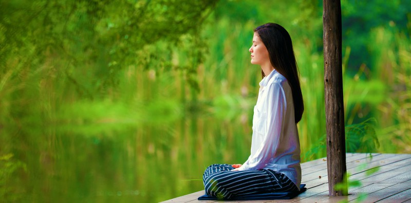 woman meditating by water