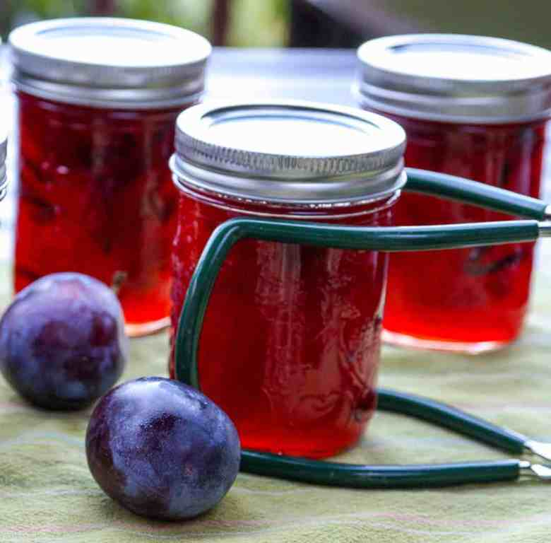 Three jars of jam and two plums on a table