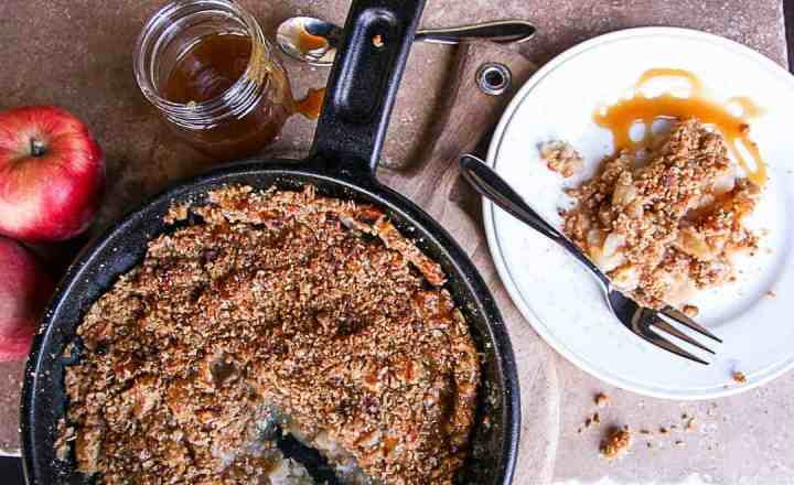 A pan of food on a table, with Apple crisp and a jar of caramel sauce