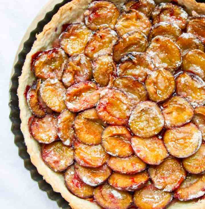 A close up of a baked plum tart in a pan