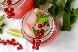 A drink garnished with red berries and a mint leaf
