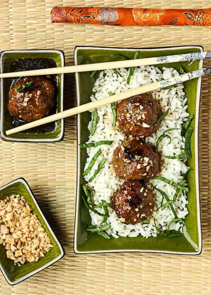 A dish of meatballs on rice, with chopsticks
