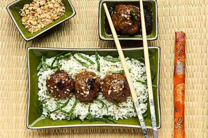 A plate of meatballs on rice, with chopsticks