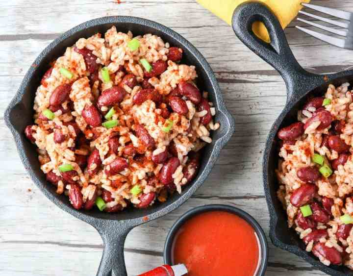 Red beans and rice in small black skillet with a small dish of hot sauce.