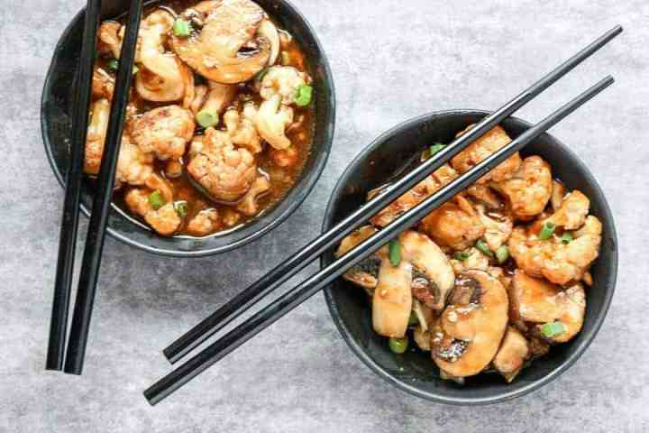 Two black bowls of food with chopsticks
