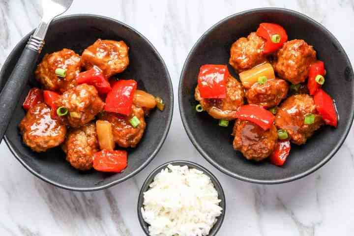 Two bowls of meatballs and a dish of rice on a table