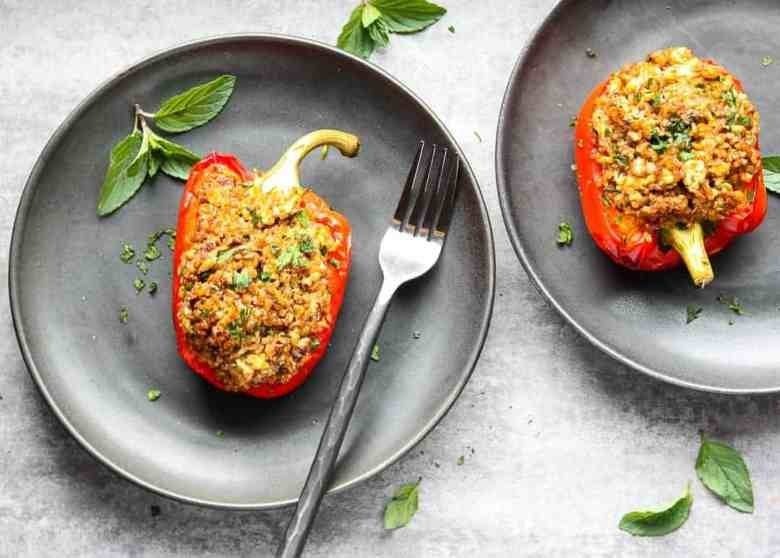 A stuffed red bell pepper on a plate with a fork