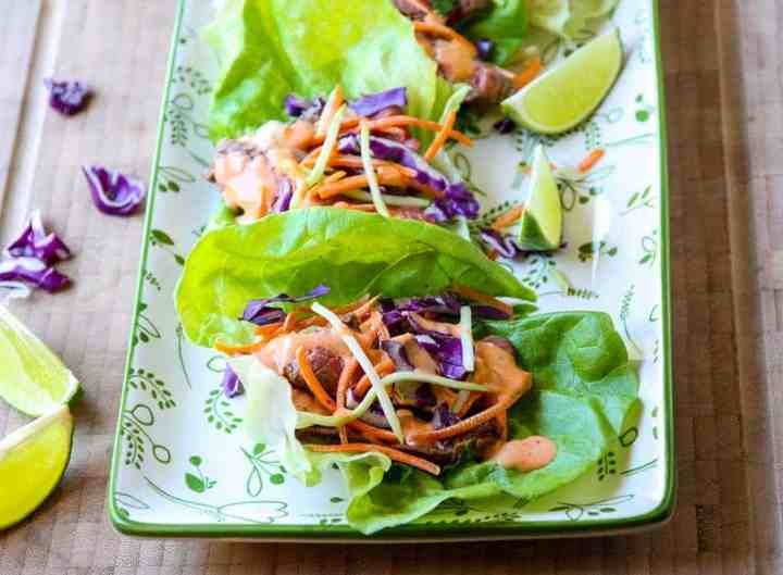 Lettuce wraps on a platter, with lime wedges