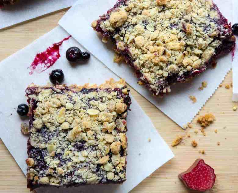 Two oatmeal bars sitting on top of a wooden cutting board