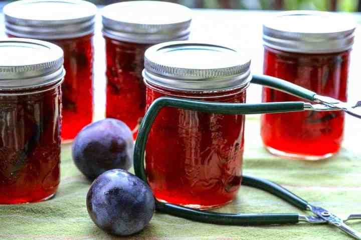 Five jars of preserves on a green kitchen towel.