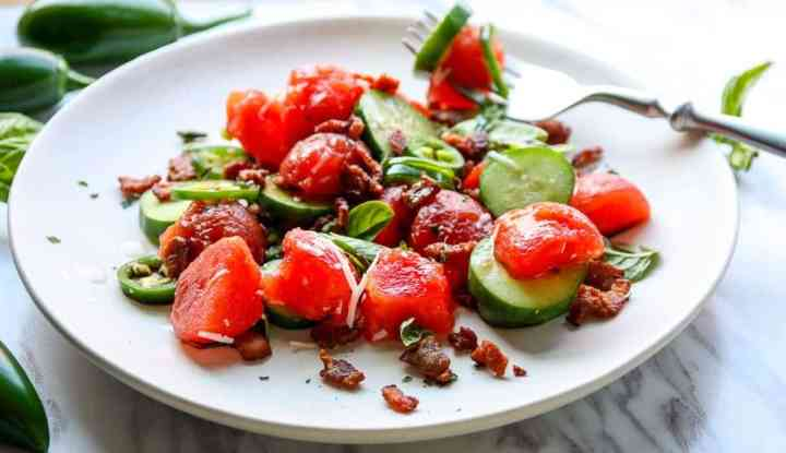 A plate of food on a table, with Salad and Watermelon