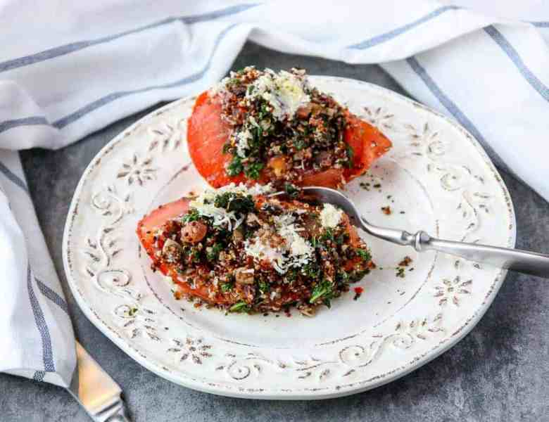 A plate of food on a table, with Quinoa and Stuffed tomatoes