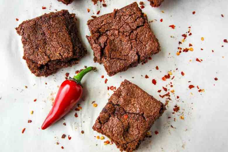 Three brownies on a plate with a chile pepper