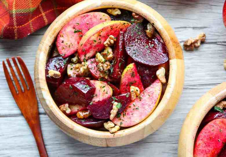A salad with apples and beets in a wooden bowl on a wooden table