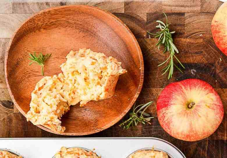 A muffin on a wooden plate with an apple