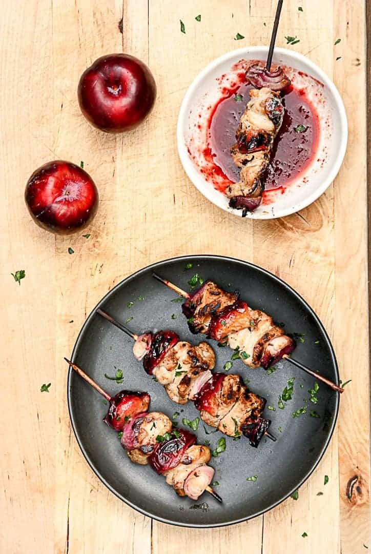 3 skewers of pork and plums on a black plate