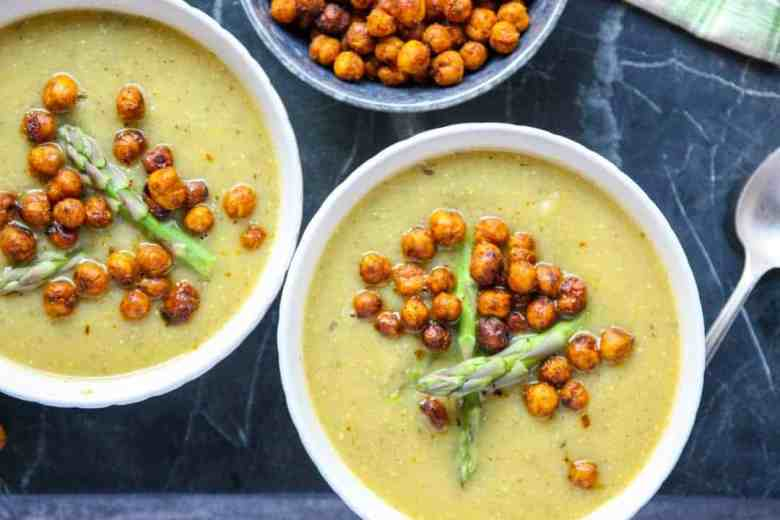 Two white bowls with cream of asparagus soup topped with chickpea croutons and asparagus tips