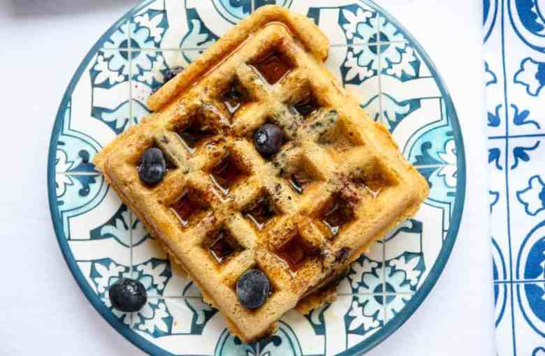 A waffle on a blue plate, with blueberries and syrup