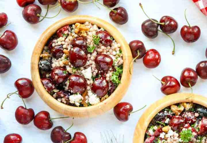 A bowl of salad sitting on top of a table, with Cherries
