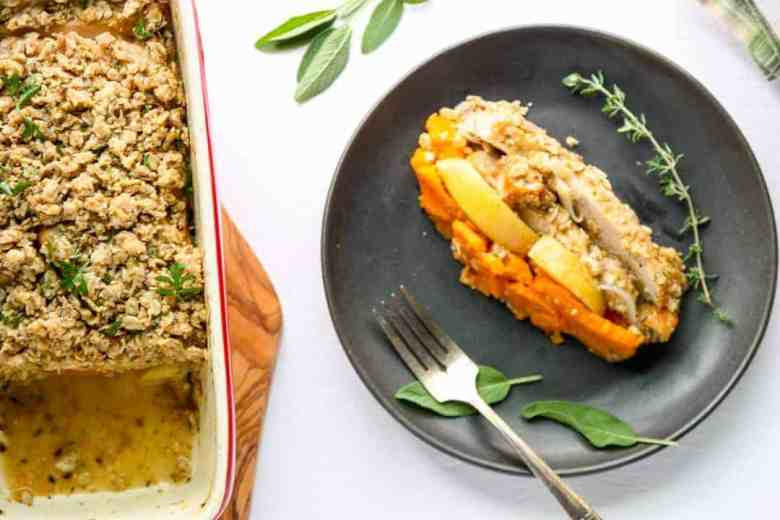 slice of casserole with layers of sweet potato, apple, and turkey on a black plate with a sprig of thyme and sage leaves