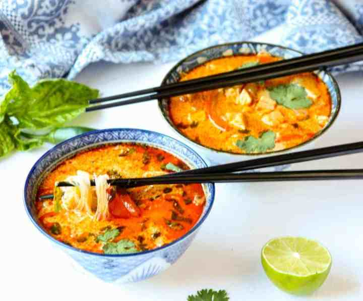 red thai curry chicken soup in two blue & white bowls with black chopsticks