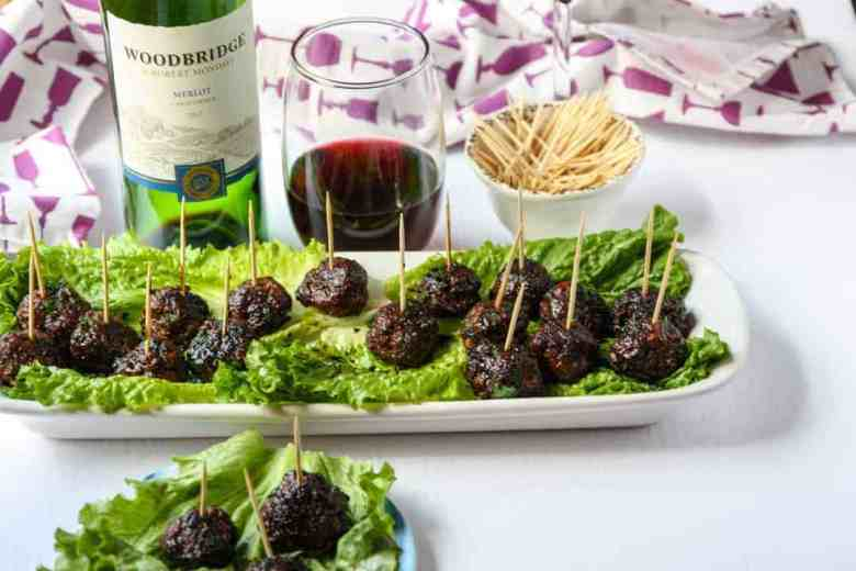 Tray of meatball appetizers on a bed of lettuce with a glass of red wine
