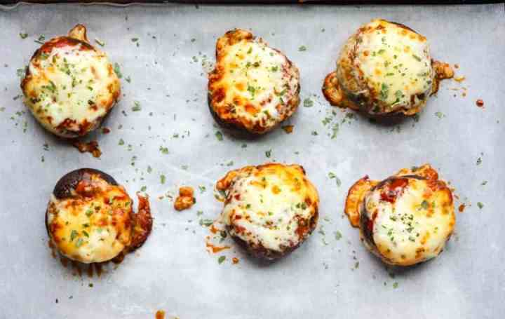 Six pizza stuffed mushrooms on a parchment lined baking sheet